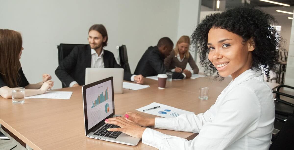 one person working on computer and facing camera, with others at large table behind her